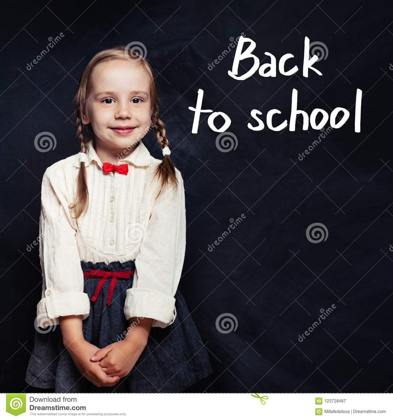 ab88f6bfc369 Cute child little girl in school uniform clothes on chalk board background.  Back to school, elementary school lesson and education concept.