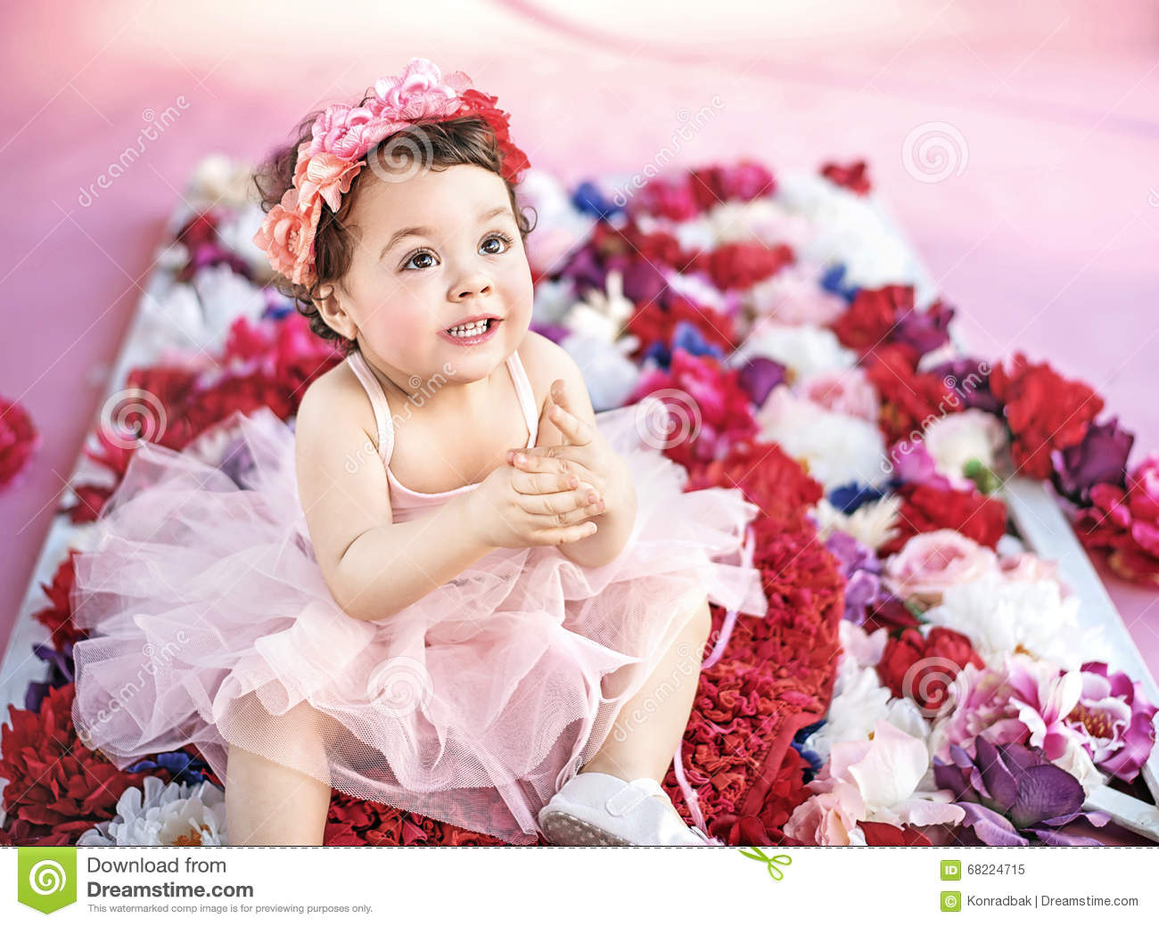 cute child sitting on a bunch of flowers stock image - image of