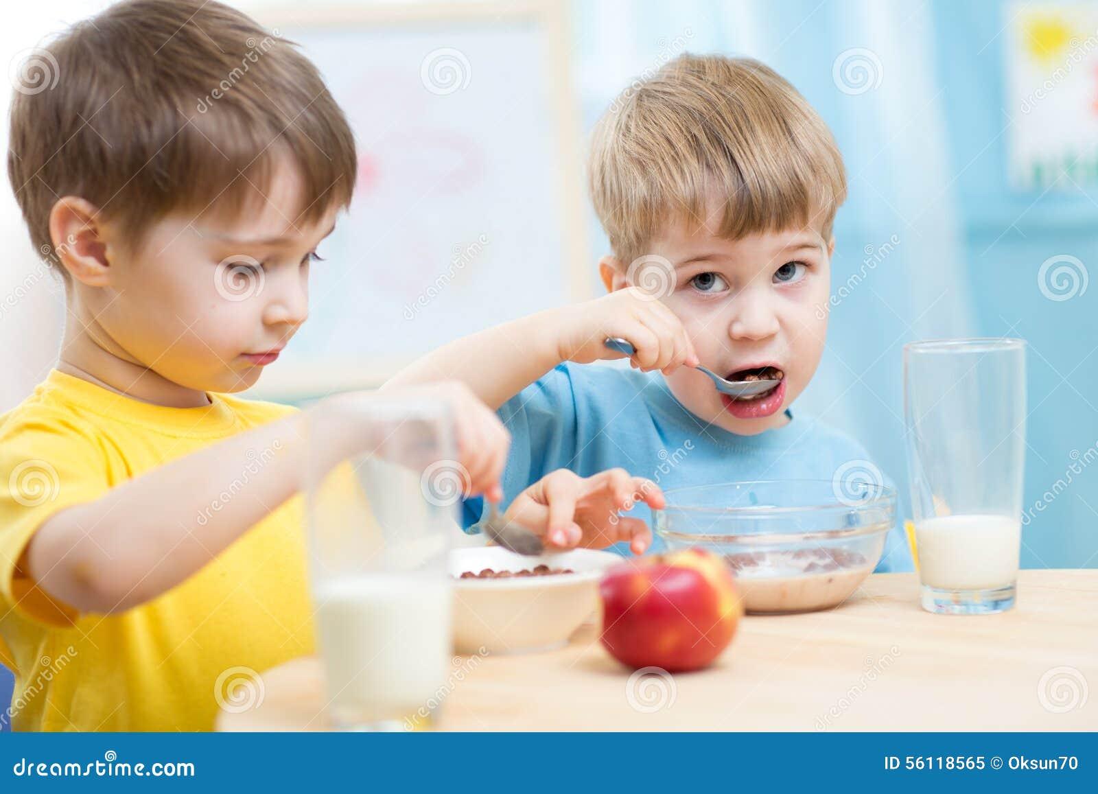 Cute children eat healthy food enjoying breakfast