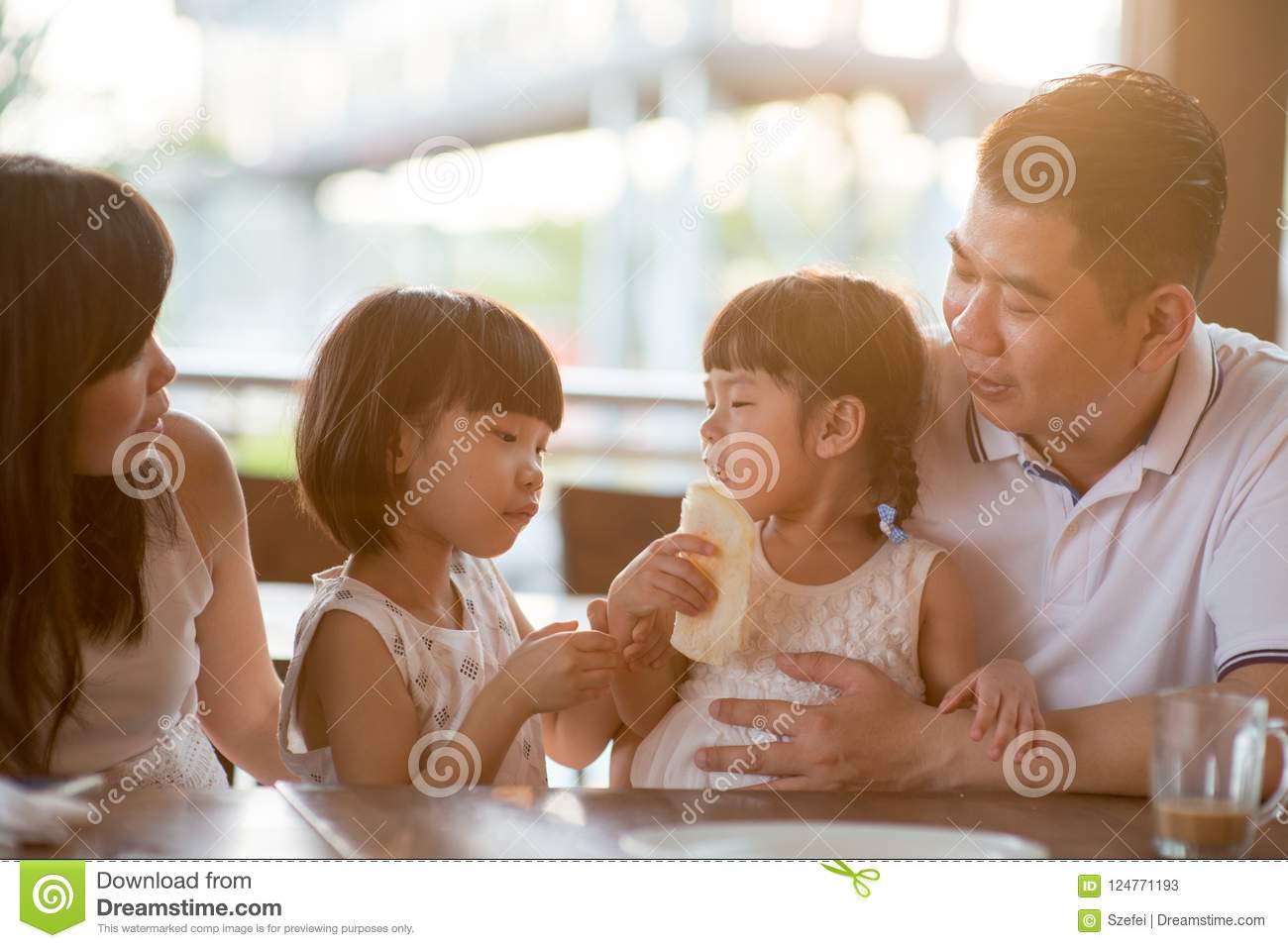 Asian family eating breakfast at cafe