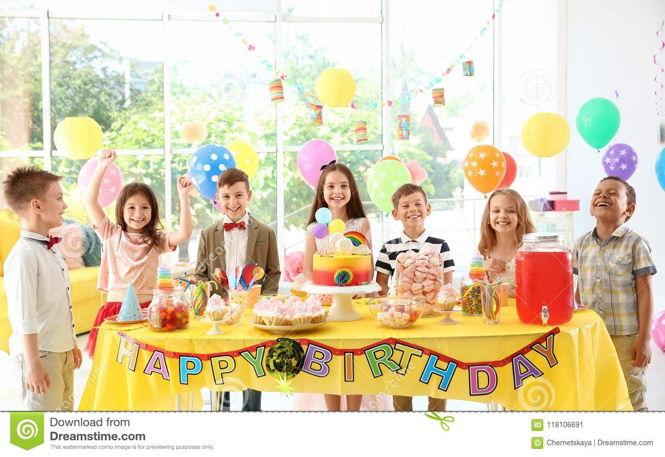 Cute children near table with treats at birthday party indoors