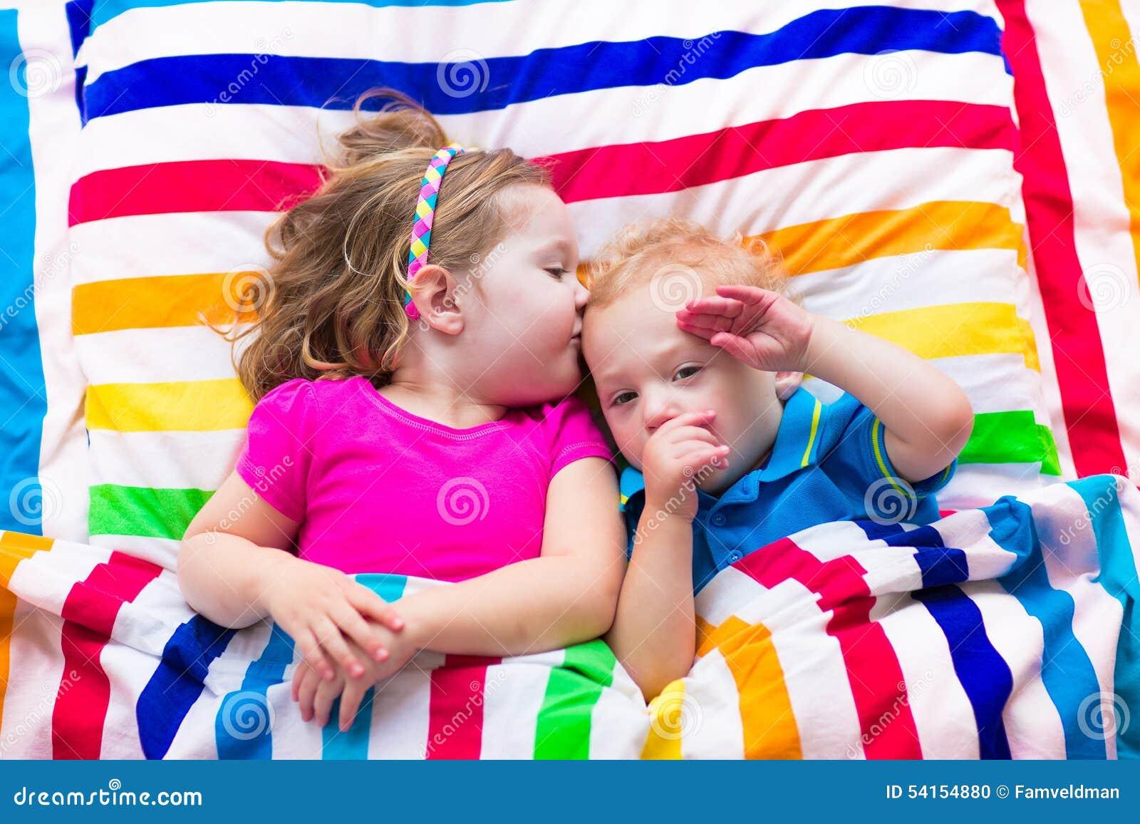 Cute Children Sleeping Under Colorful Blanket Stock Photo
