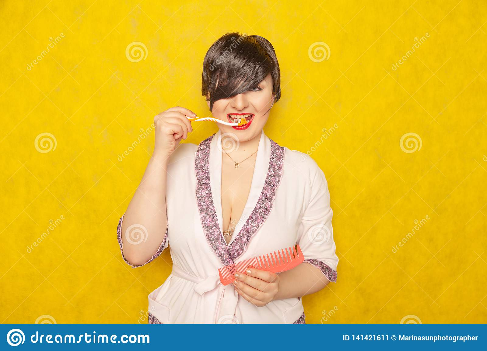 Cute chubby girl in a pink robe stands with a comb and toothbrush on a yellow background in the Studio