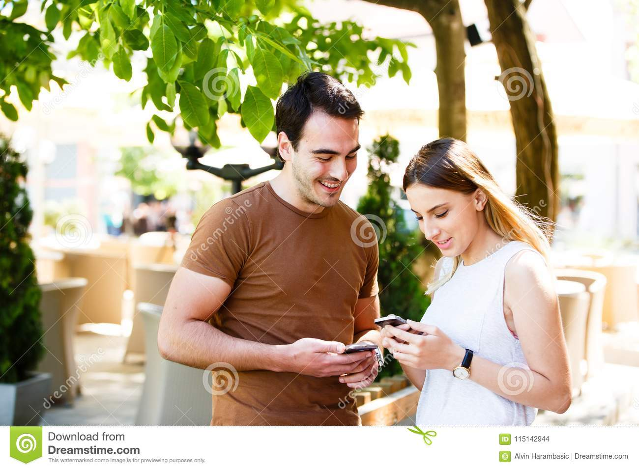Cute young couple standing and using phone