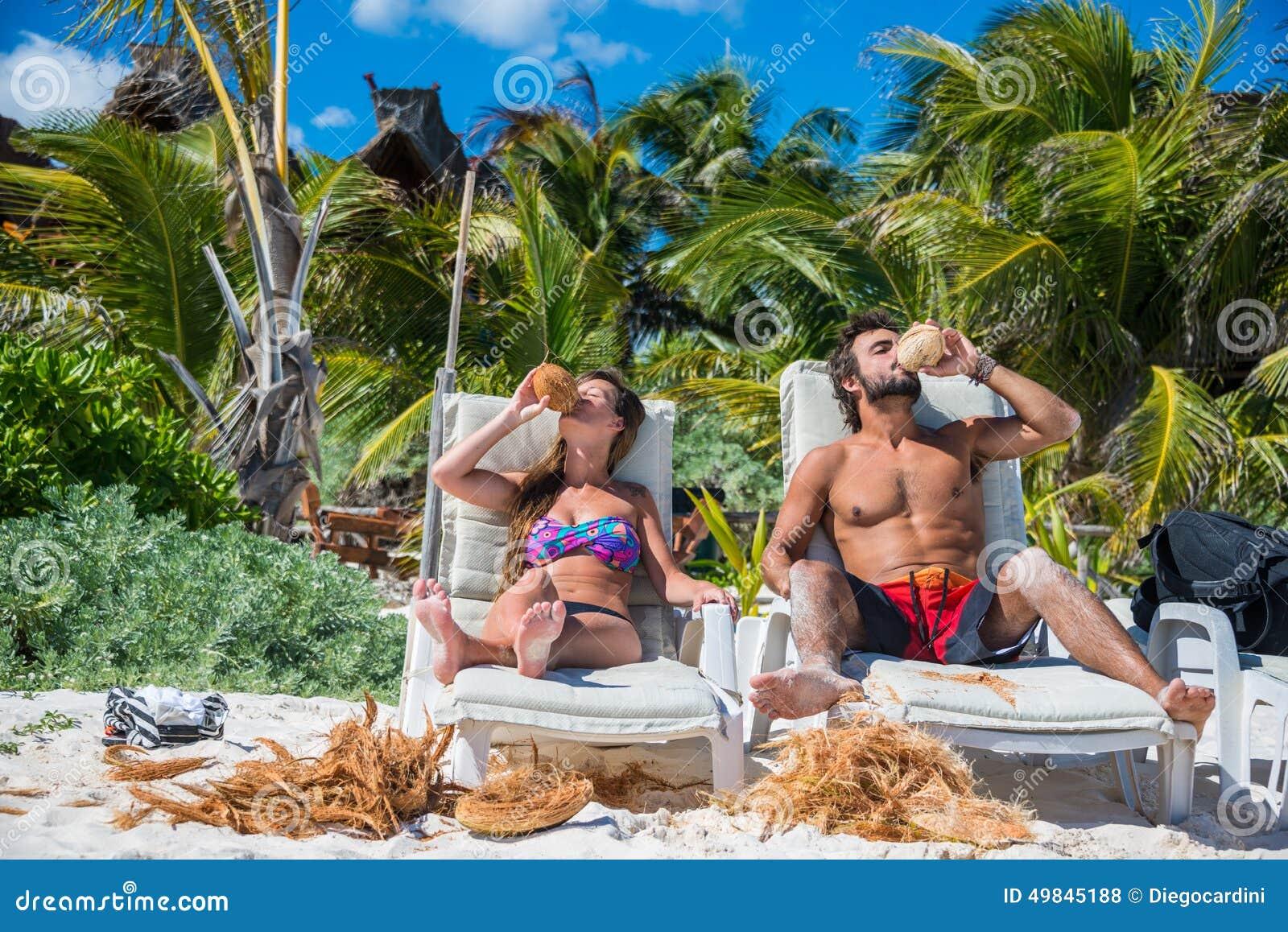 Cute Couple drinking Coconut at Tulum caribbean beach. Riviera M