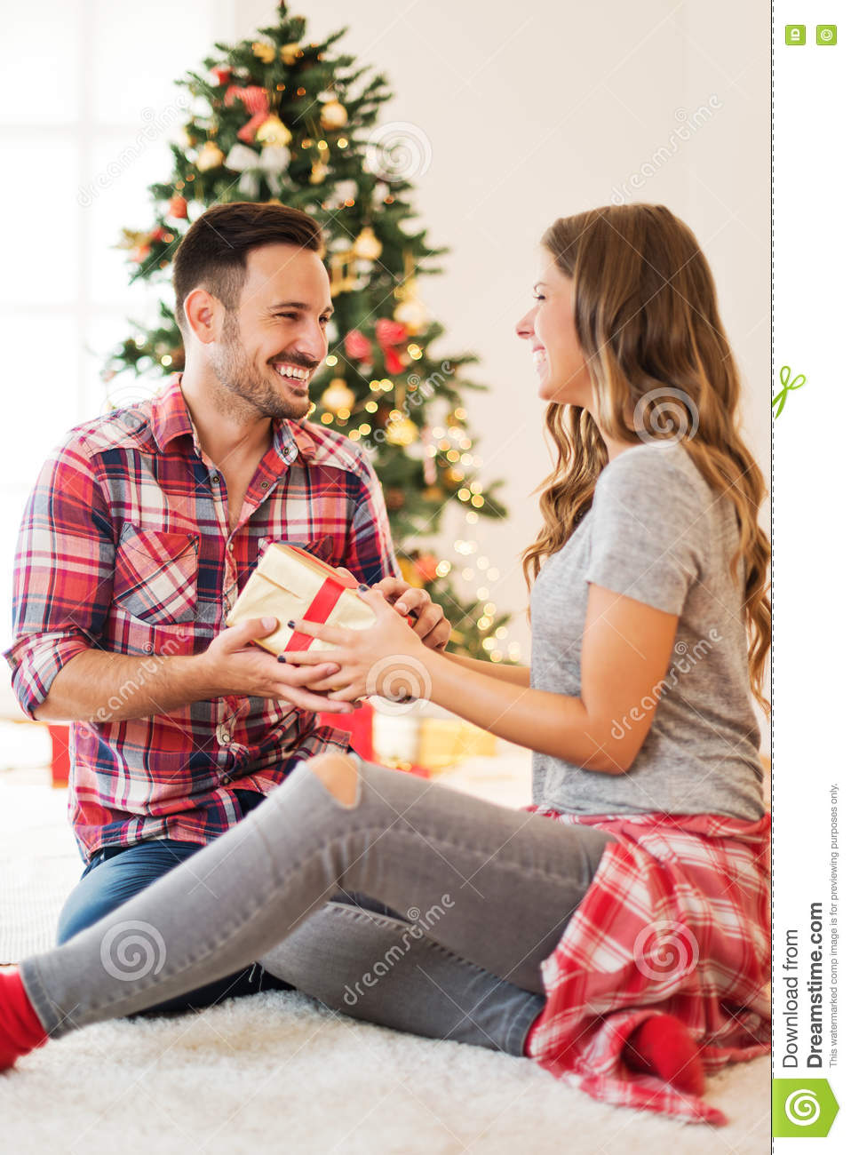 Cute couple exchanging Christmas presents on Christmas morning