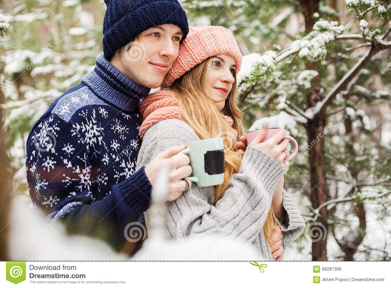 cute couple with hot tea in cups in forest among fir trees