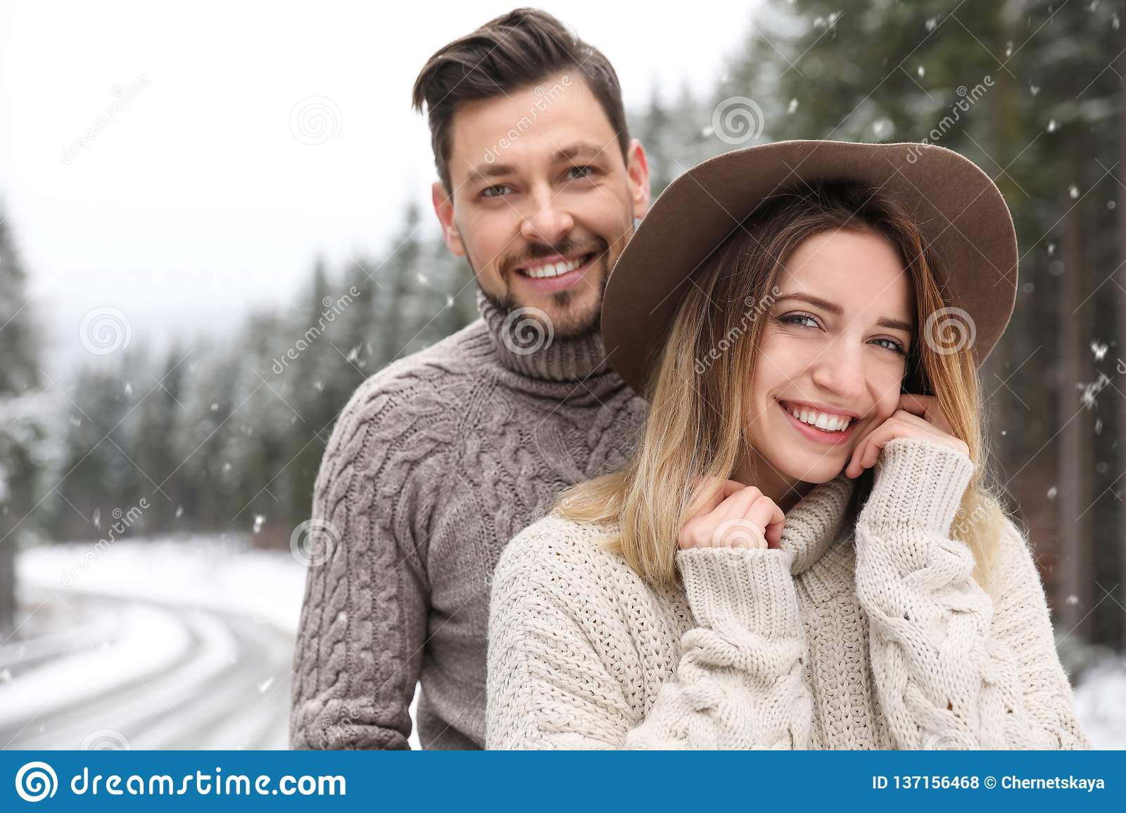 Cute couple outdoors on snowy day. Winter