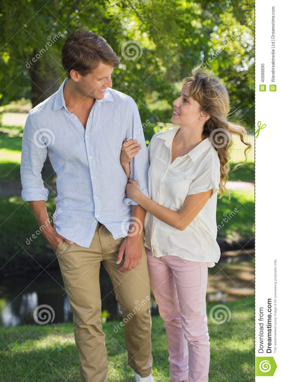 Cute Couple Walking Arm In Arm In The Park Smiling At Each ...