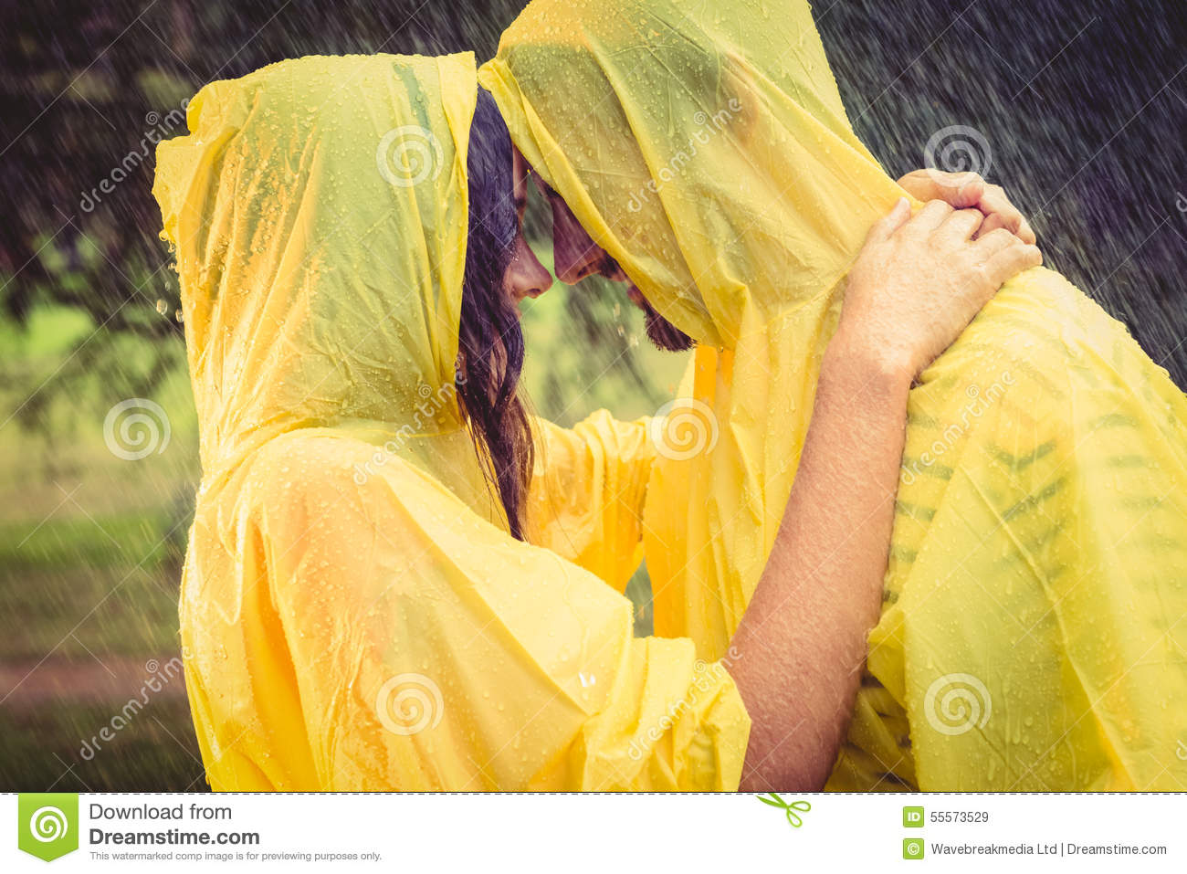 Cute couple wearing protection cape and hugging under the rain in the park royalty free