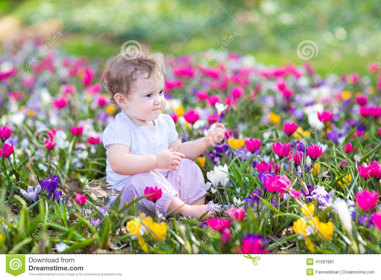 Cute curly little baby sitting between beautiful spring flowers