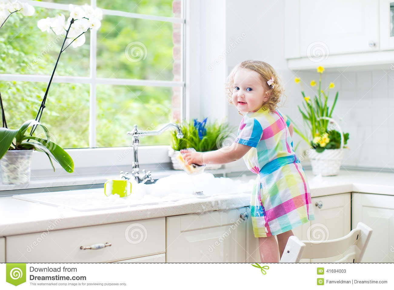 Cute curly toddler girl in colorful dress washing dishes