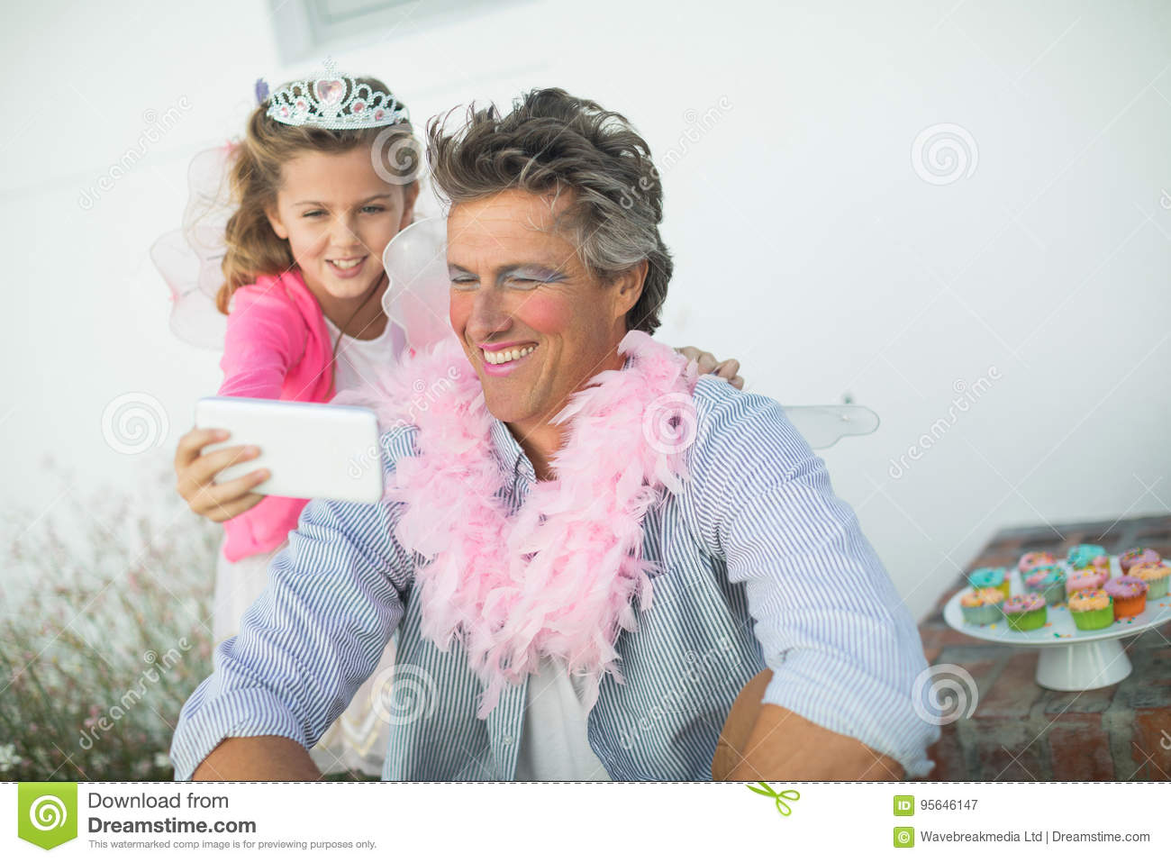 Cute daughter in fairy costume showing mobile phone to father