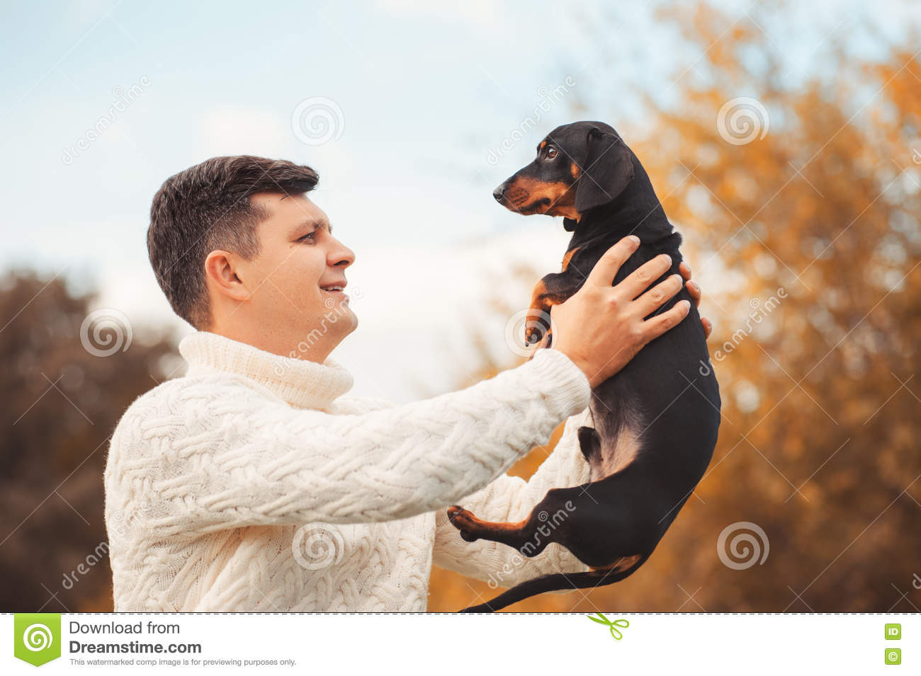 Cute dog and his owner young handsome man have fun in the park, conceptions animals, pets
