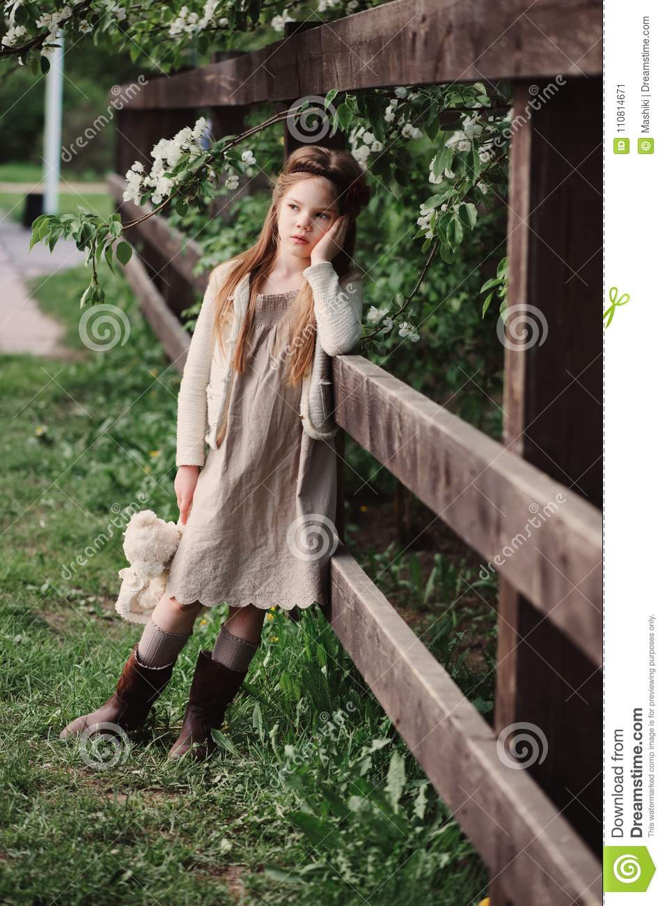 Cute dreamy child girl posing at rustic wooden fence with teddy bear