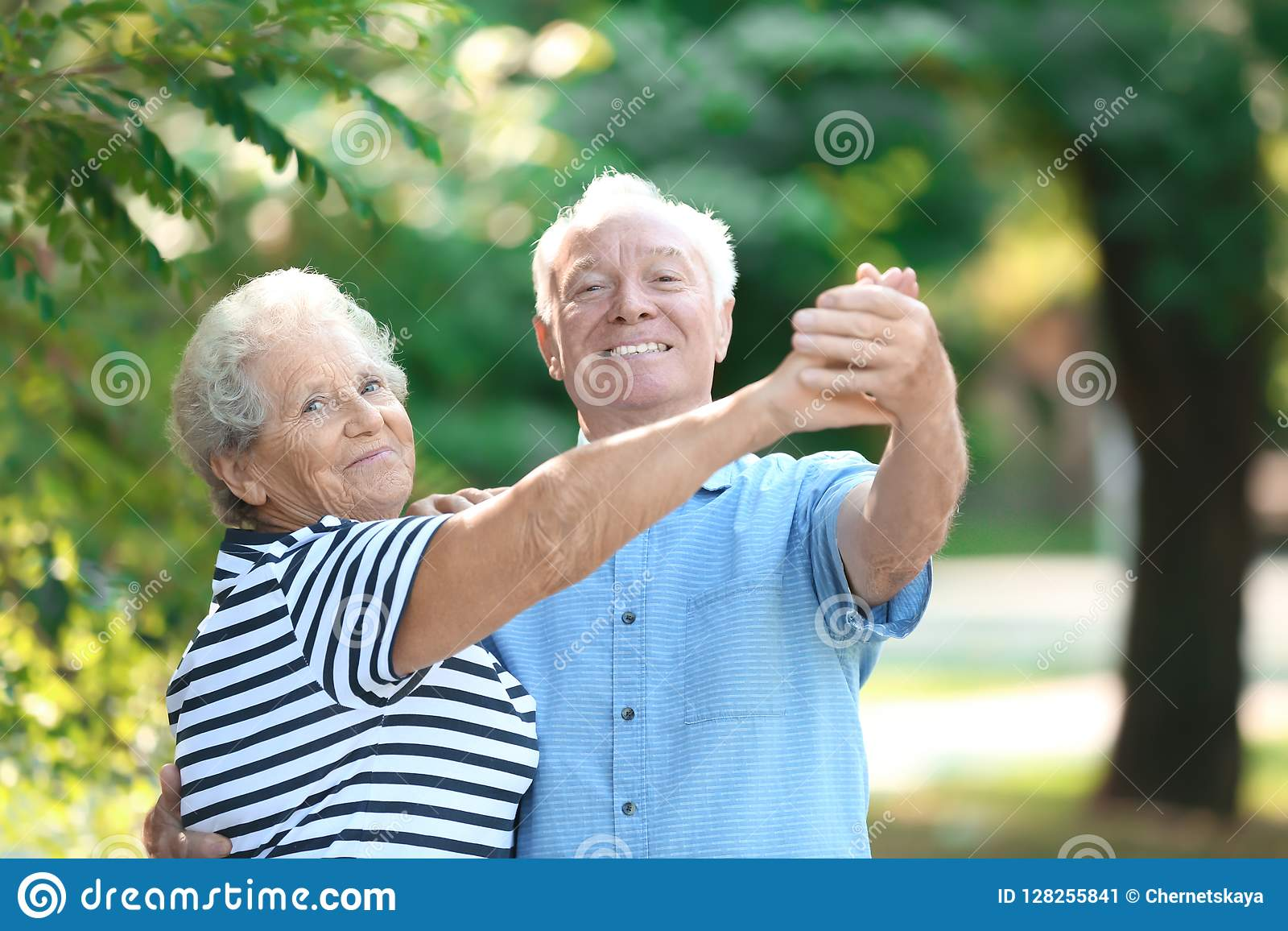 Cute elderly couple dancing outdoors.