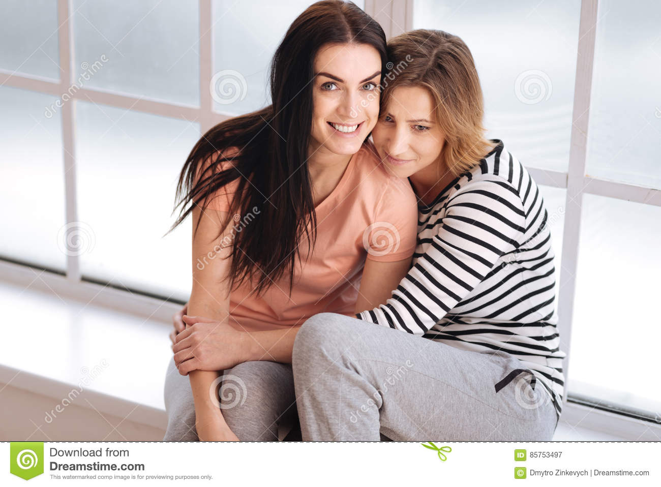 cute emotional couple sitting on a window sill stock image - image