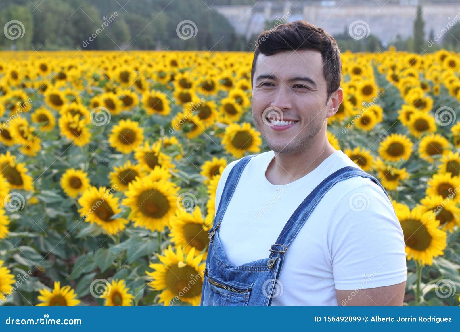 Cute ethnic farmer in sunflower field