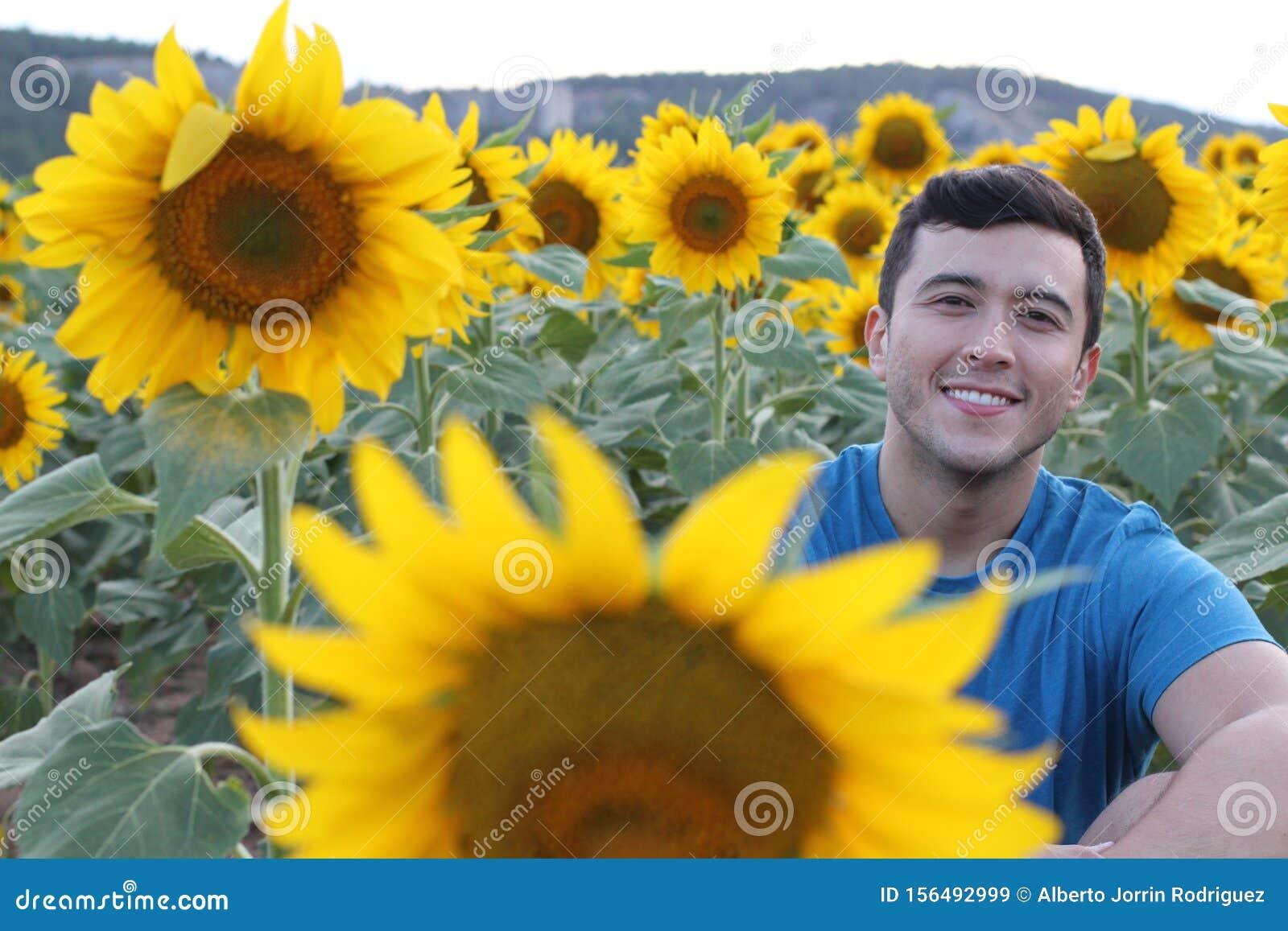 Cute ethnic man in sunflower field