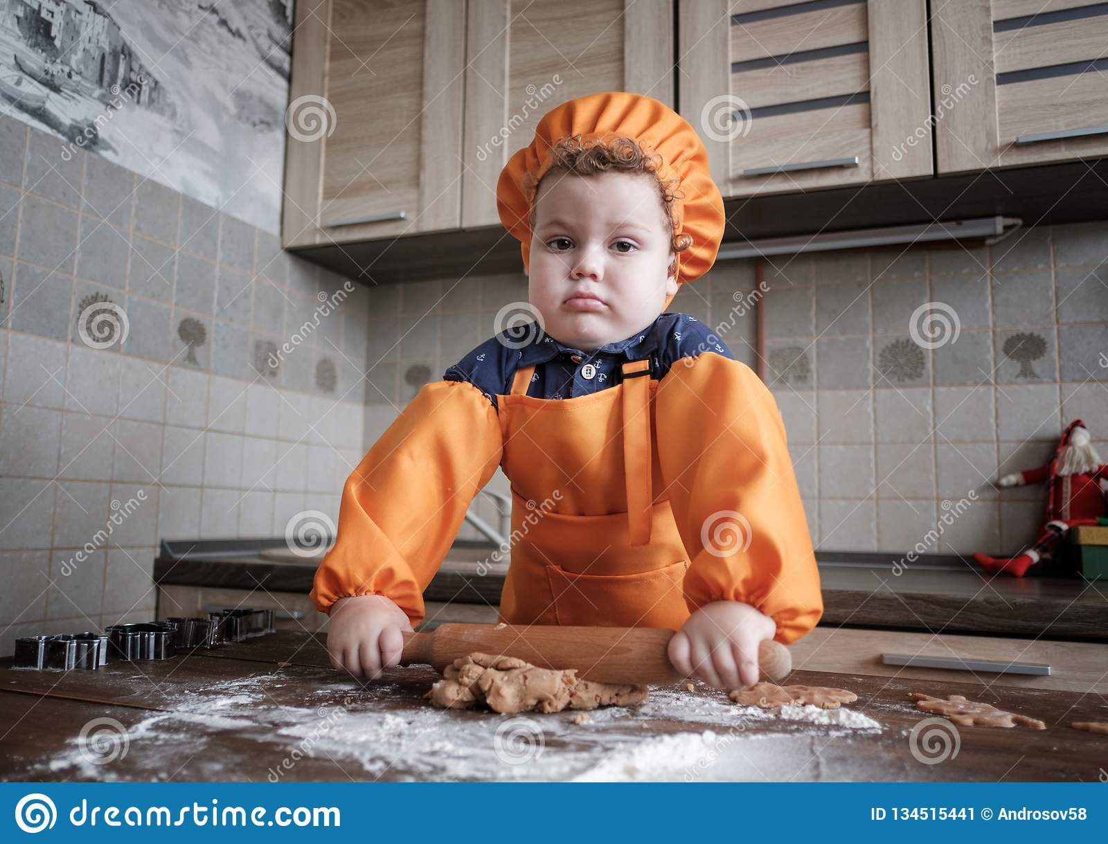 Cute European boy in a suit of the cook makes ginger cookies