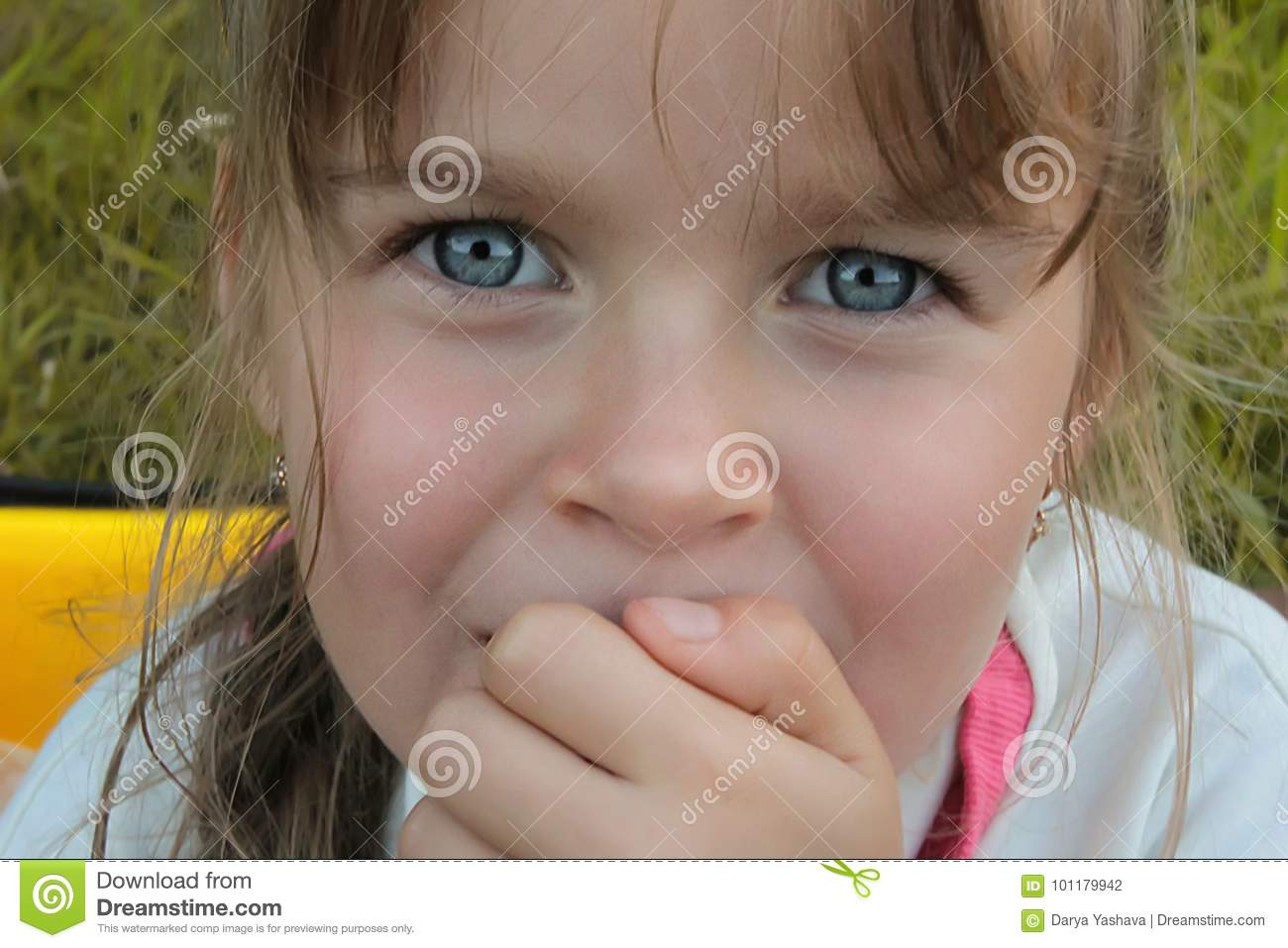 A cute European/Caucasian little girl with big with blue expressive eyes looking directly into the camera. Close-up