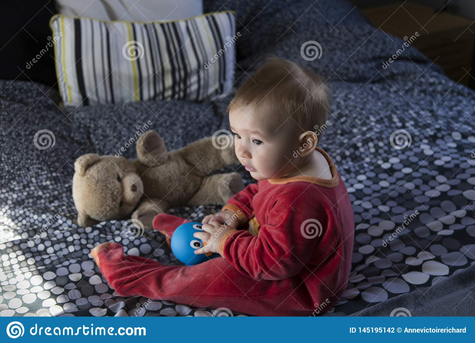 Cute fair baby girl sitting on bed playing with large blue rubber duck and vintage teddy bear