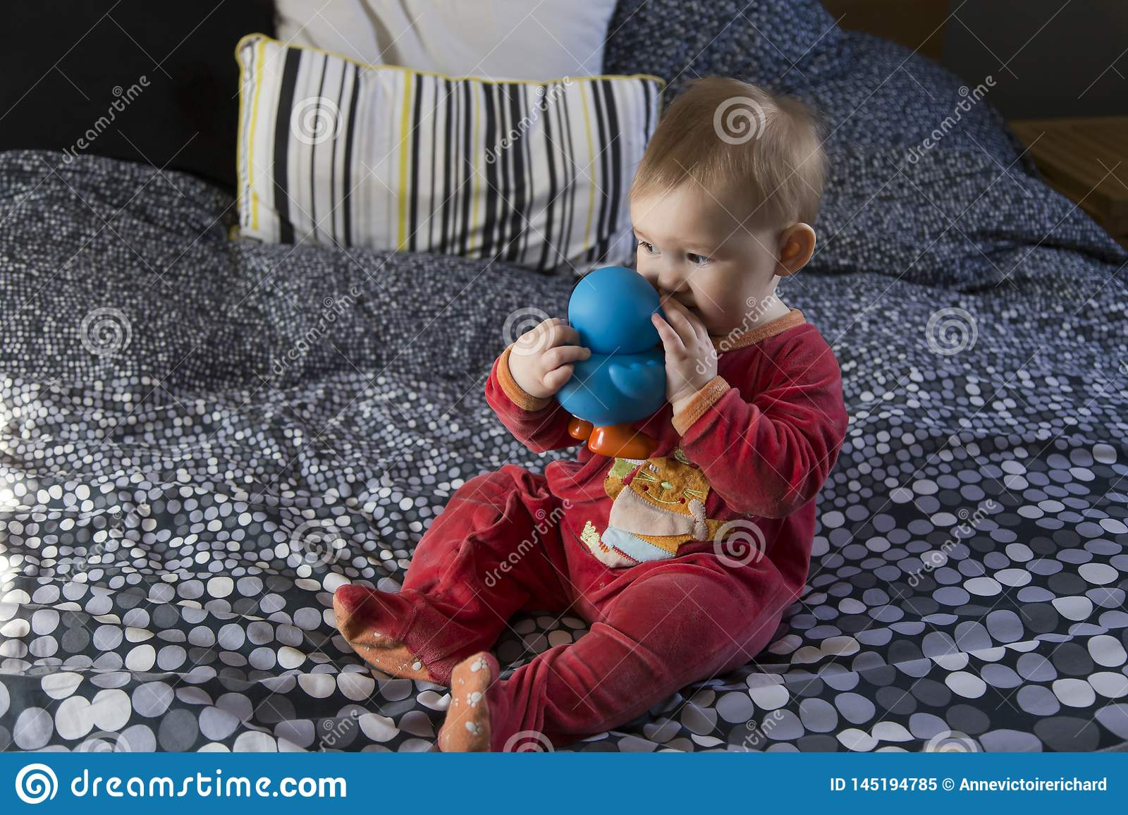 Cute fair baby girl sitting on bed sucking on large blue rubber duck
