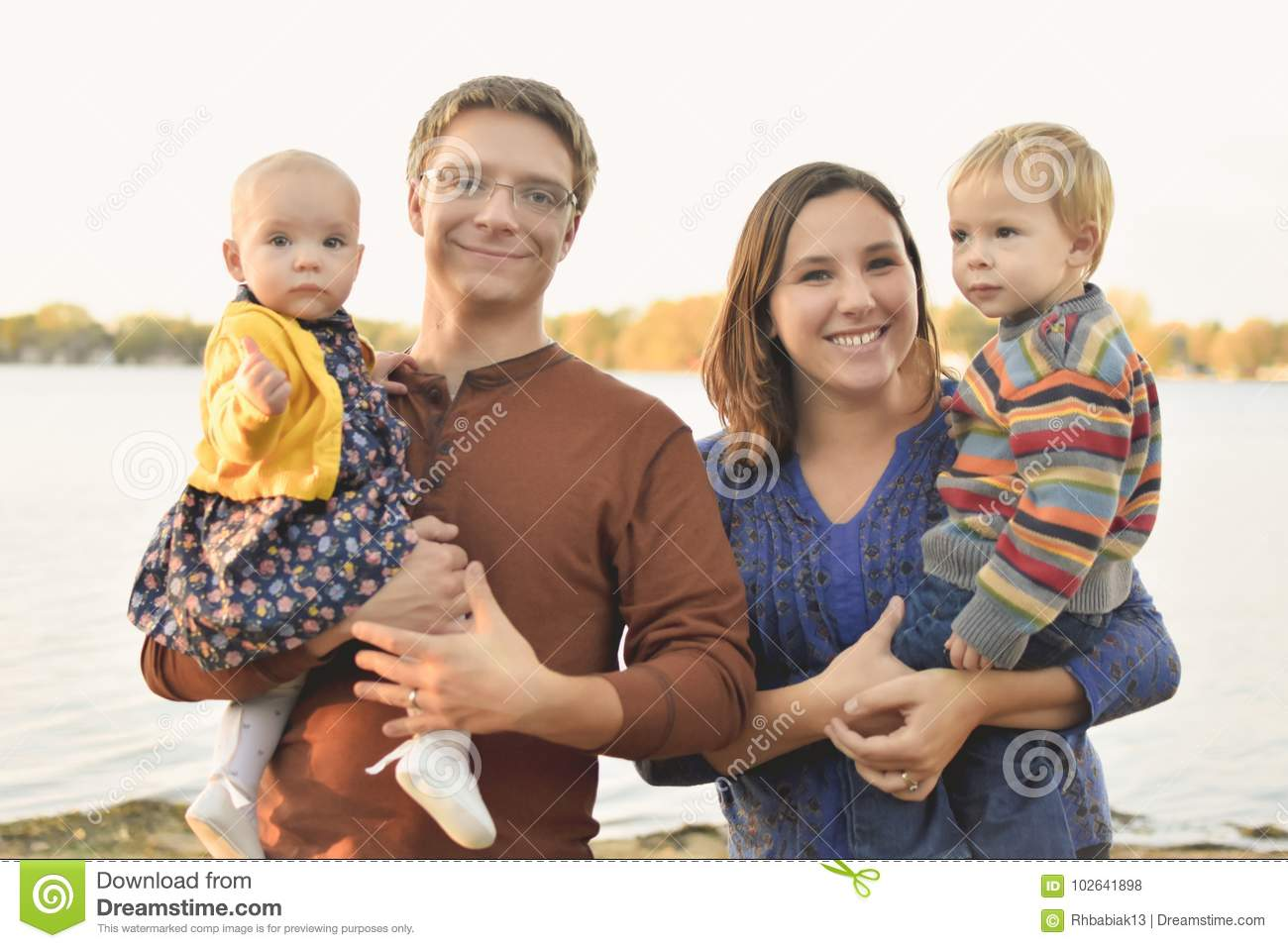 A cute family with a mom dad little boy and little baby girl together by the lake in the fall family of four american dream