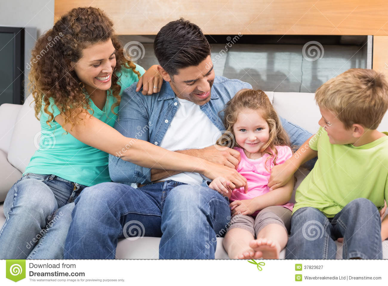 Cute family tickling little girl on the couch