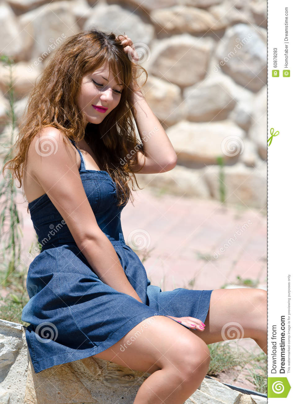 cute fashion woman sitting on the edge of the wall stock image