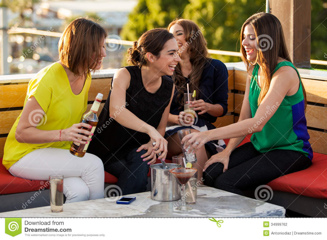 Cute female friends having drinks stock photography for The terrace group