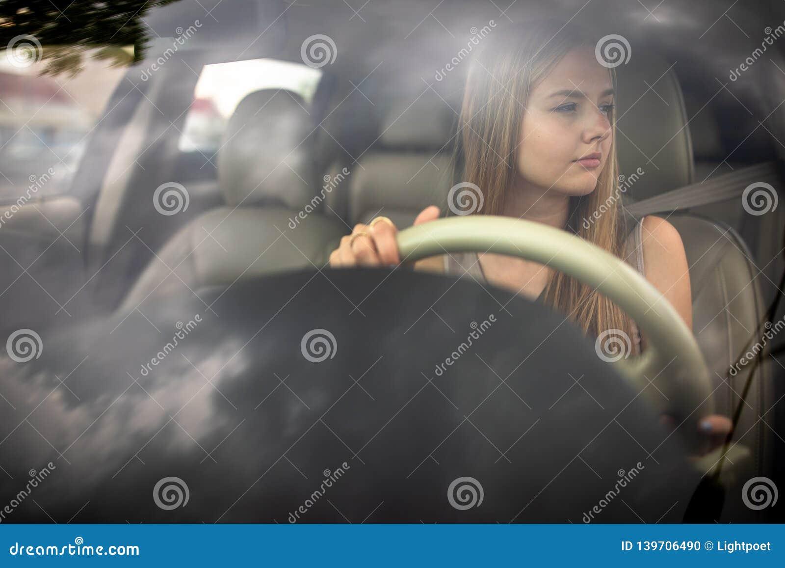 Cute female teen driver enjoying her freshly acquired driving license