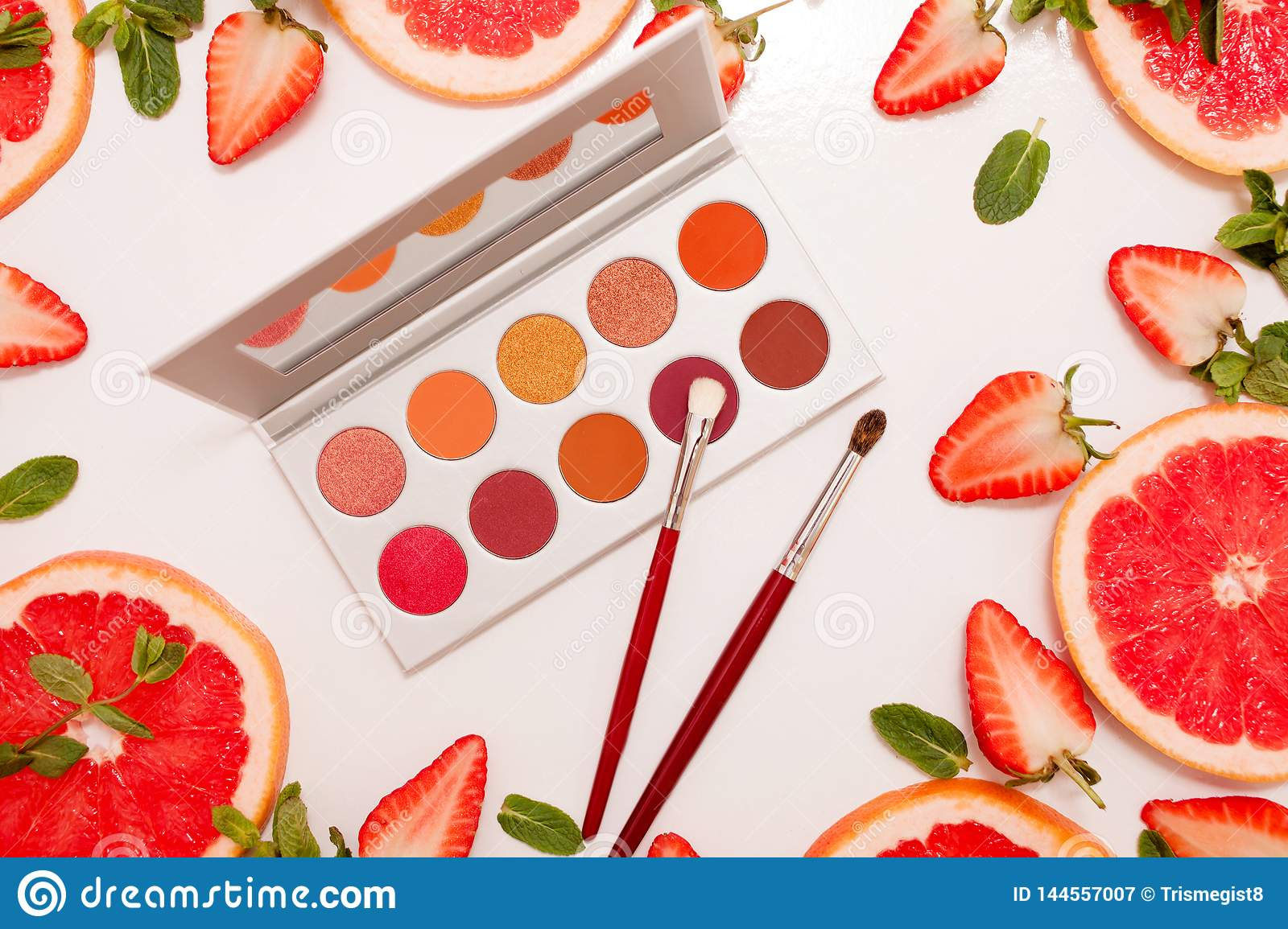 Cute flat lay with palette of cosmetics with fresh fruit, cut strawberries and grapefruit or red orange, mint leaves