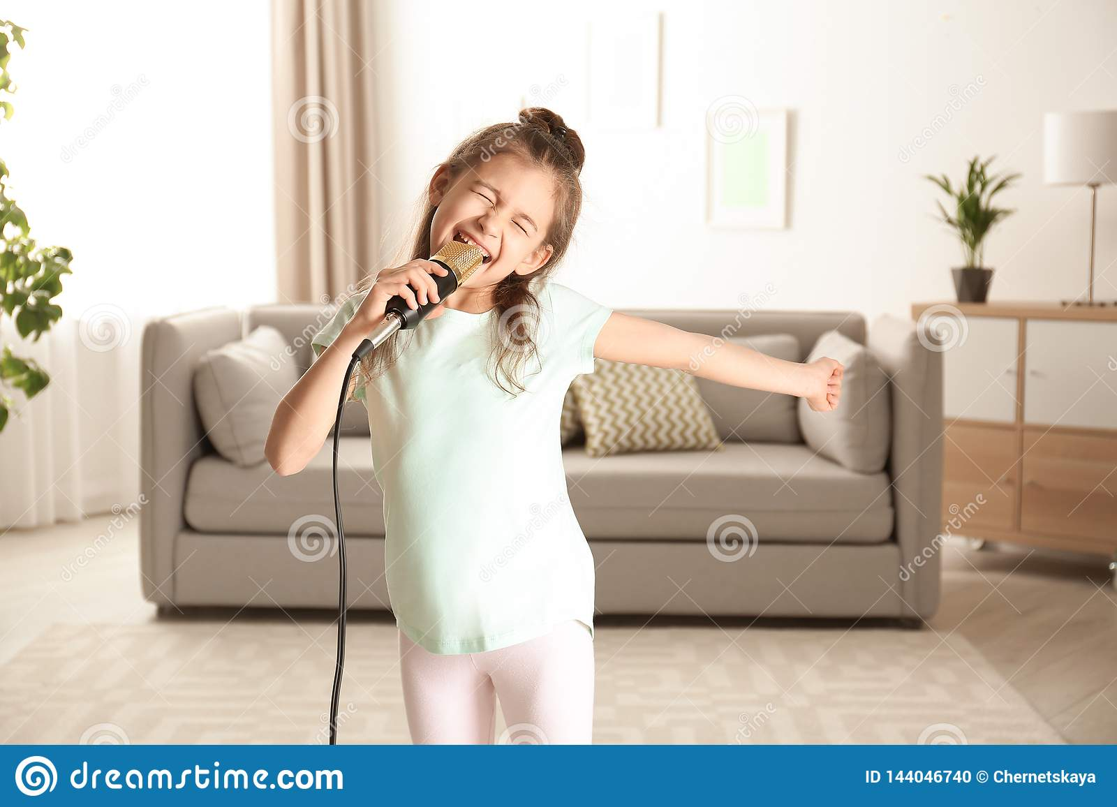 Cute funny girl with microphone in room