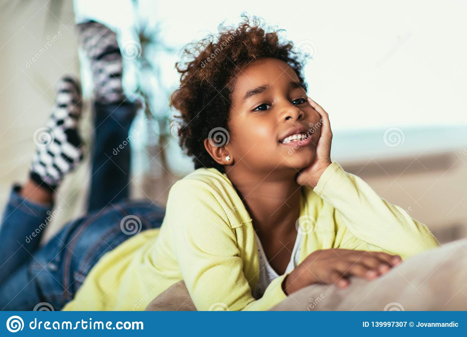 Funny little african american girl looking at camera, smiling mixed race child posing for portrait at home