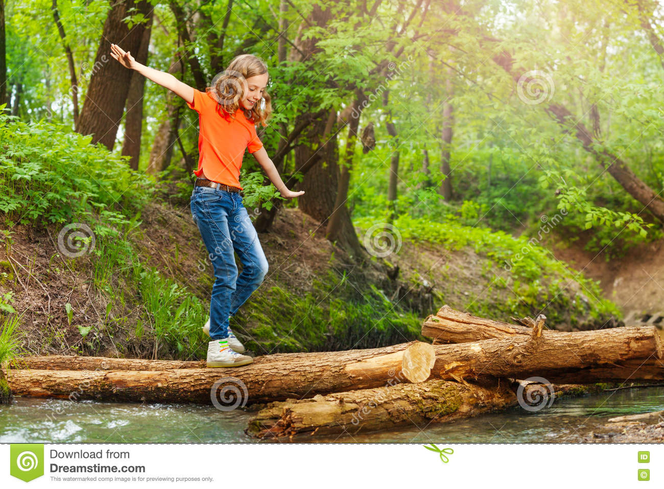 Cute girl balancing while crossing a log bridge