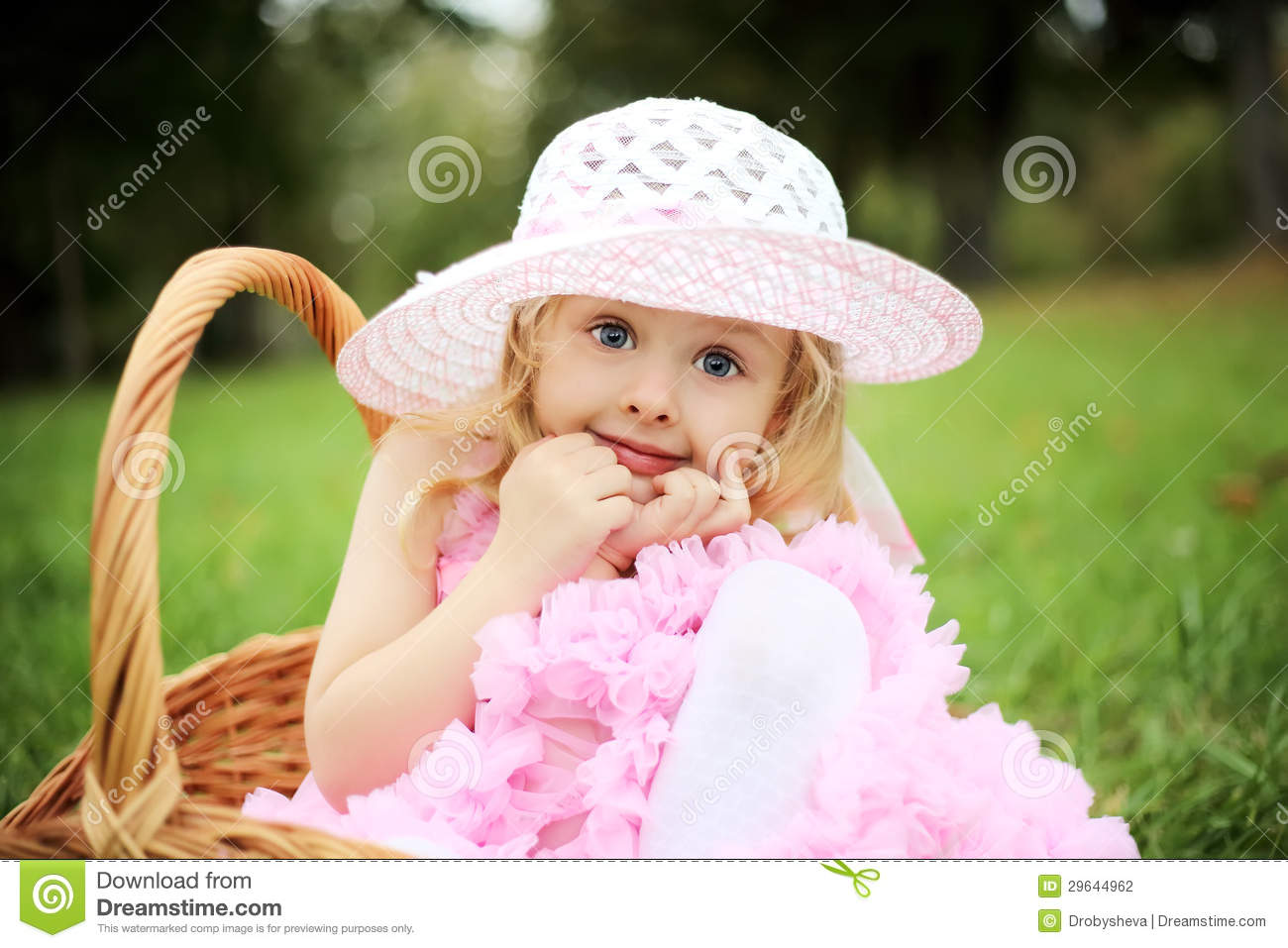 Cute girl in a beautiful dress in a basket in a summer pa