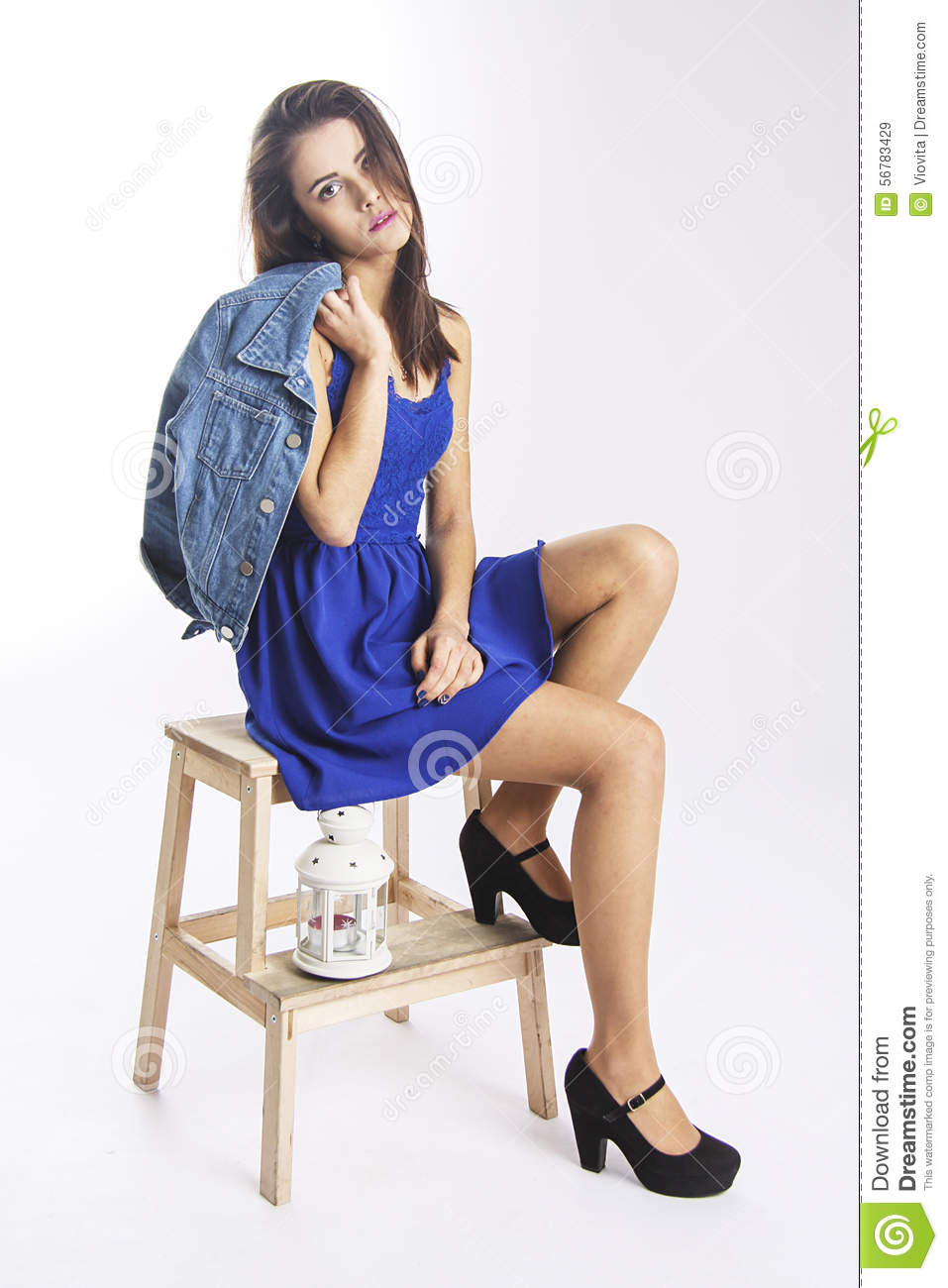 Cute girl in blue jacket on wooden chair