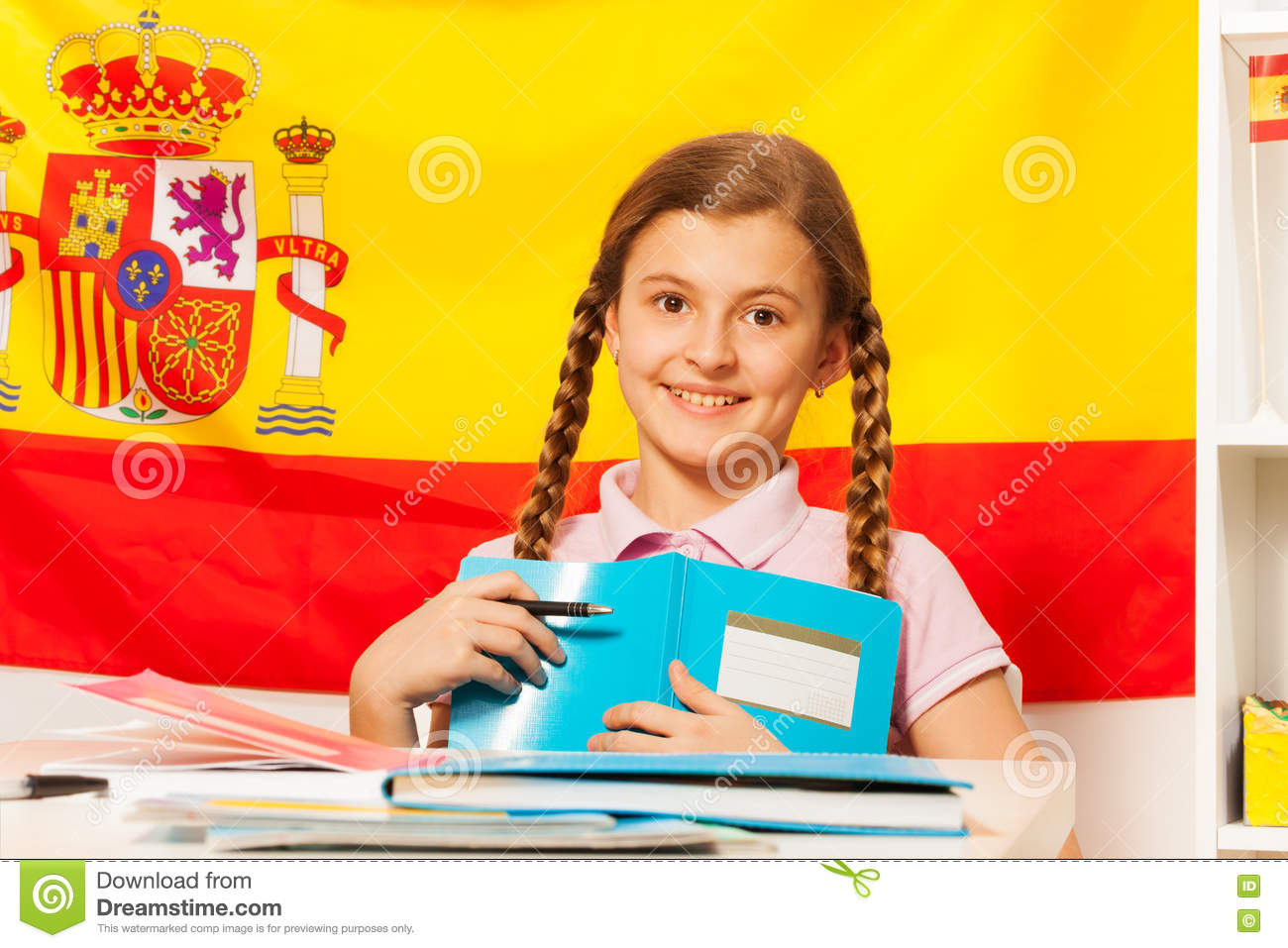 cute with book and the spanish flag behind stock image