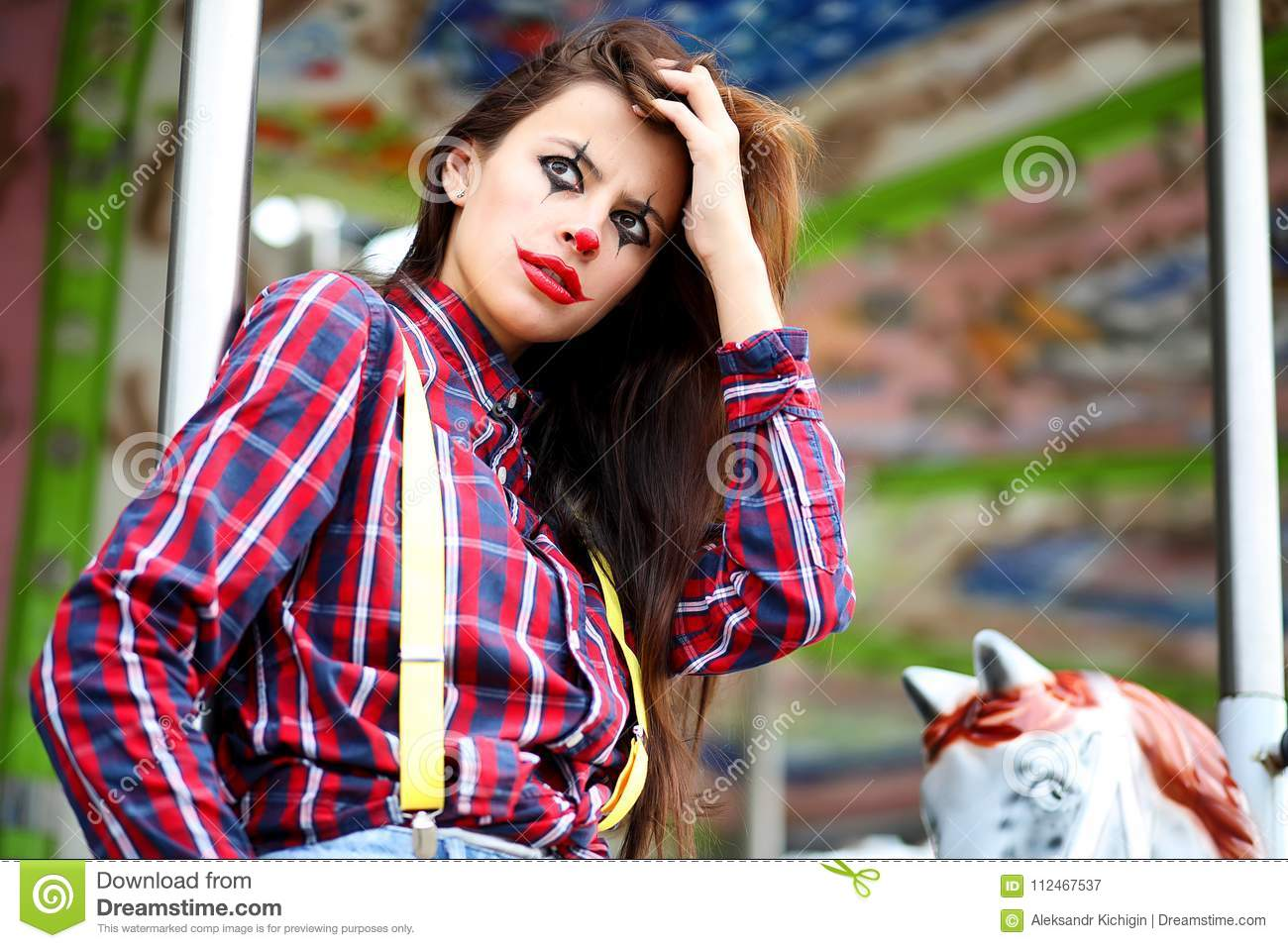 Cute girl in a clown makeup on a background of a fair