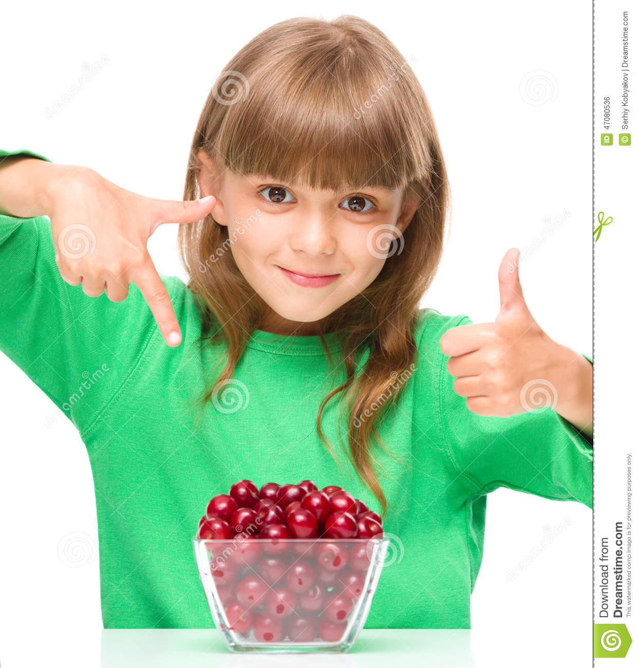 Cute girl is eating cherries showing thumb up sigh