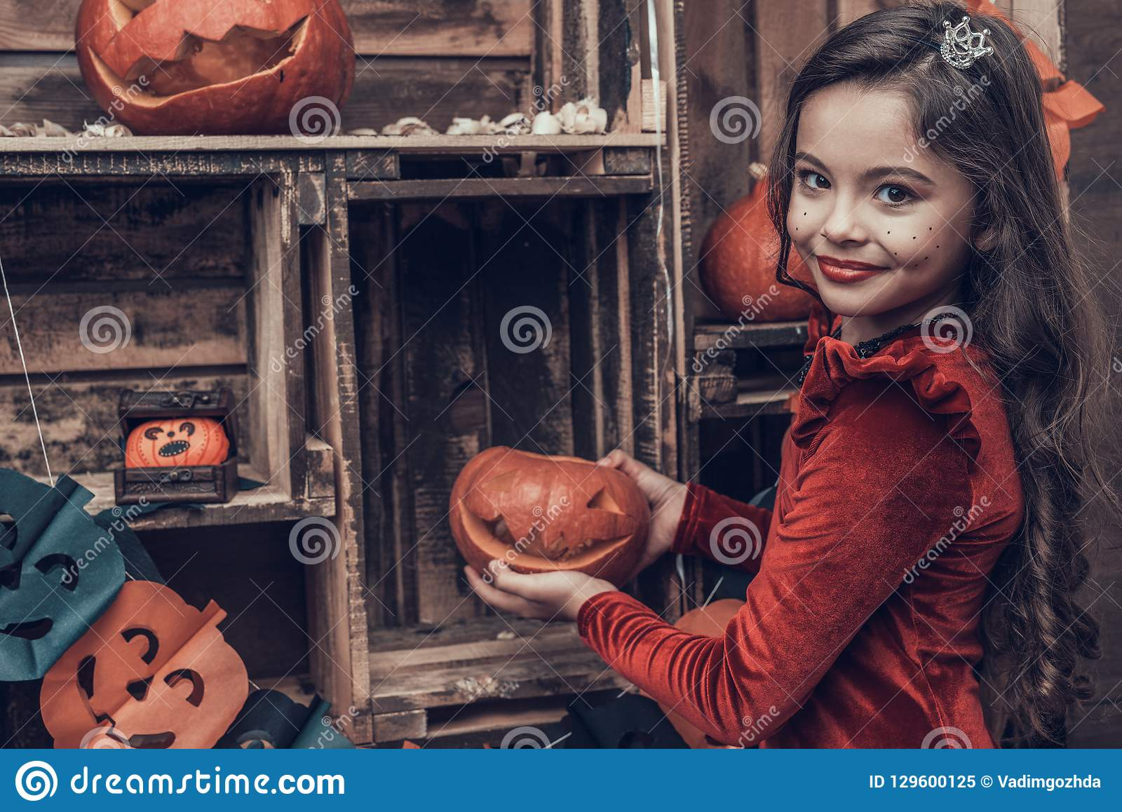 Cute Girl in Halloween Costume with Carved Pumpkin
