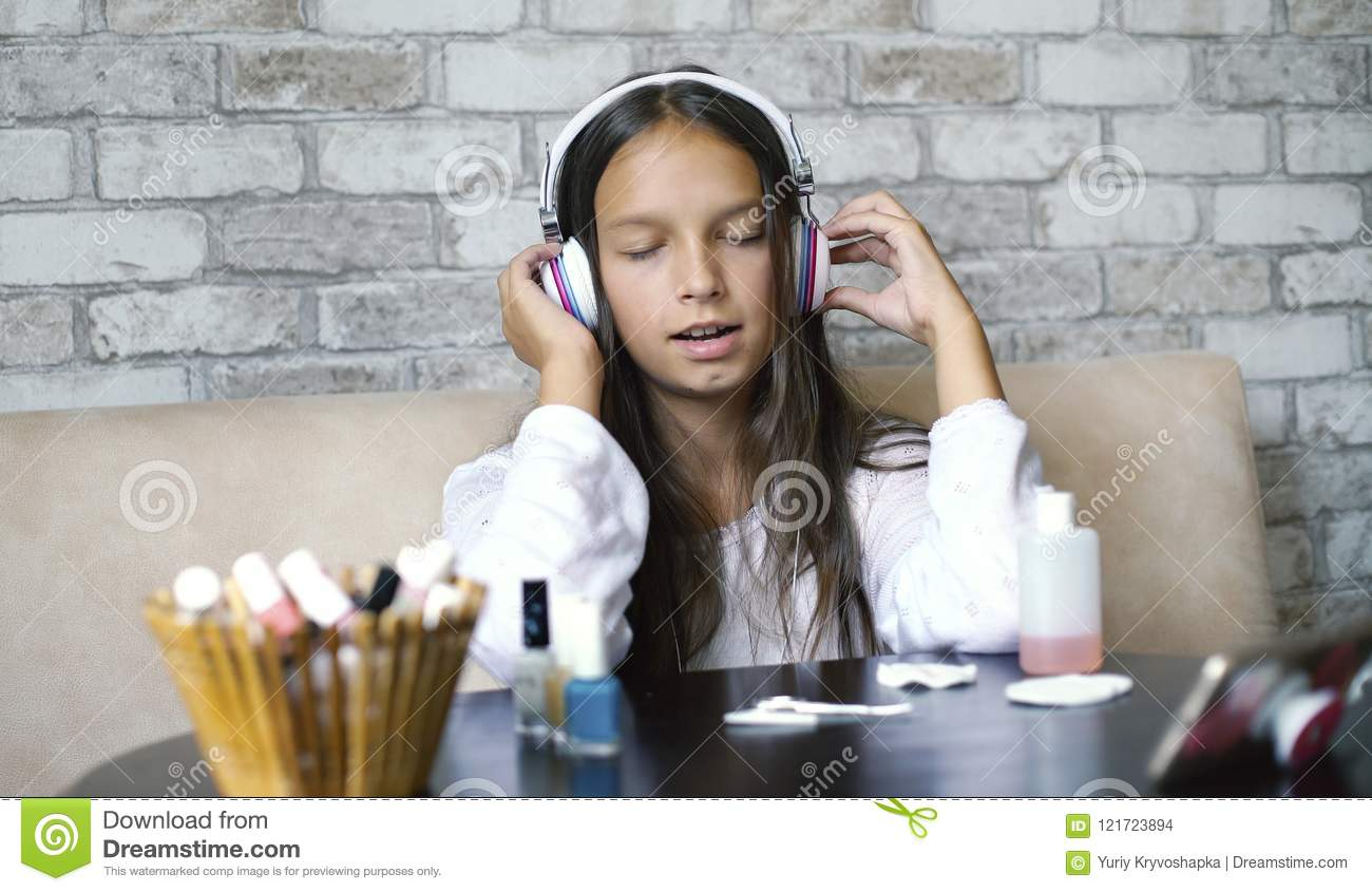 Cute Girl In Headphones And Home Clothes Listening Music On Phone And Singing While Making ...