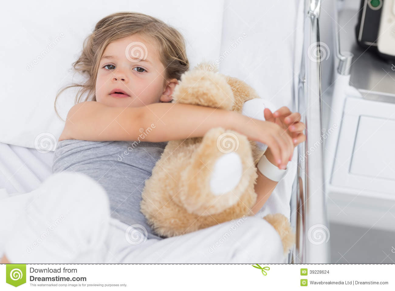 Cute girl hugging teddy bear in hospital bed Stock Images