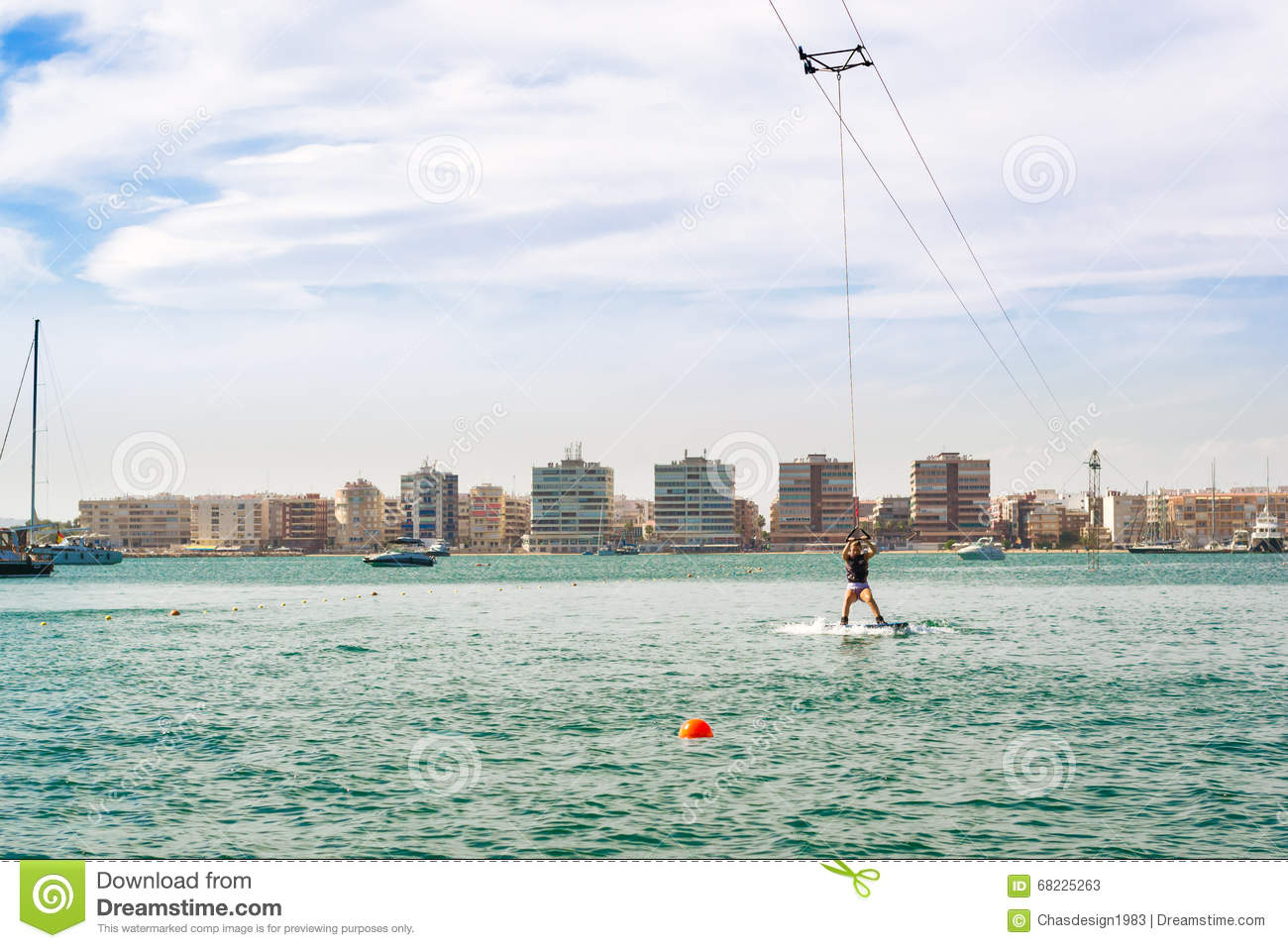 Cute girl learns to surf on background of yachts in marina - Z yachting torrevieja ...