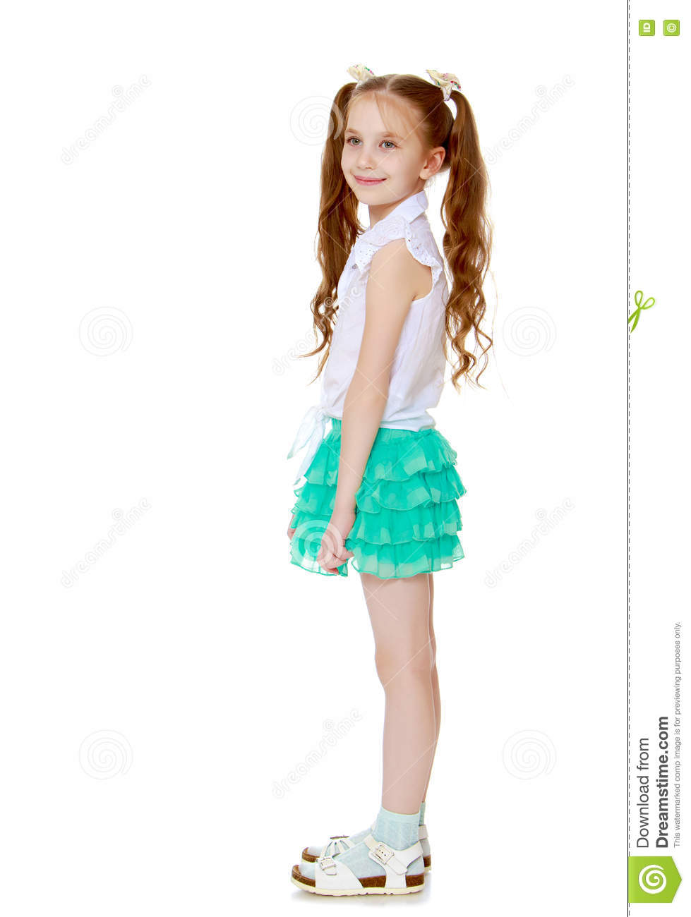 Caucasian little girl with long hair to the waist which wire braided white  ribbons. In a white shirt without a pattern and green short skirt.