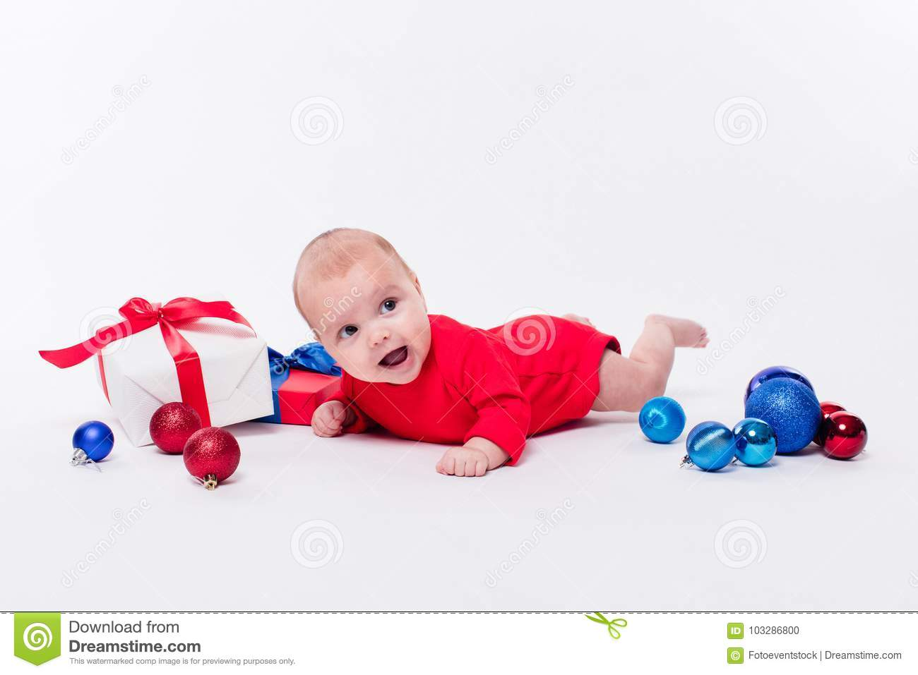 6332c26e235c Cute girl lying on her stomach on a white background in a New Year`s cap  among Christmas balls, blue and red boxes with gifts, picture with depth of  field