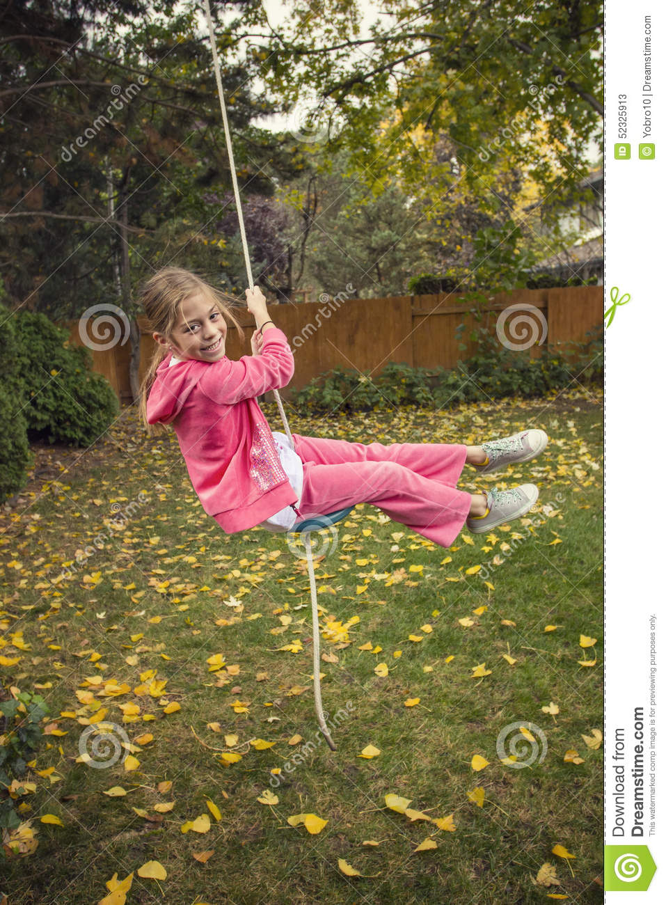Cute Girl Playing On A Backyard Rope Swing Outdoors Stock ...