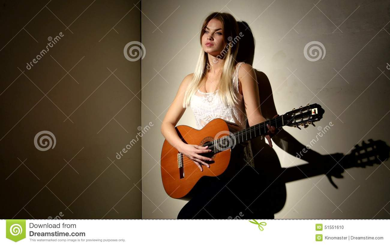 cute girl plays on the acoustic guitar with bright stock footage