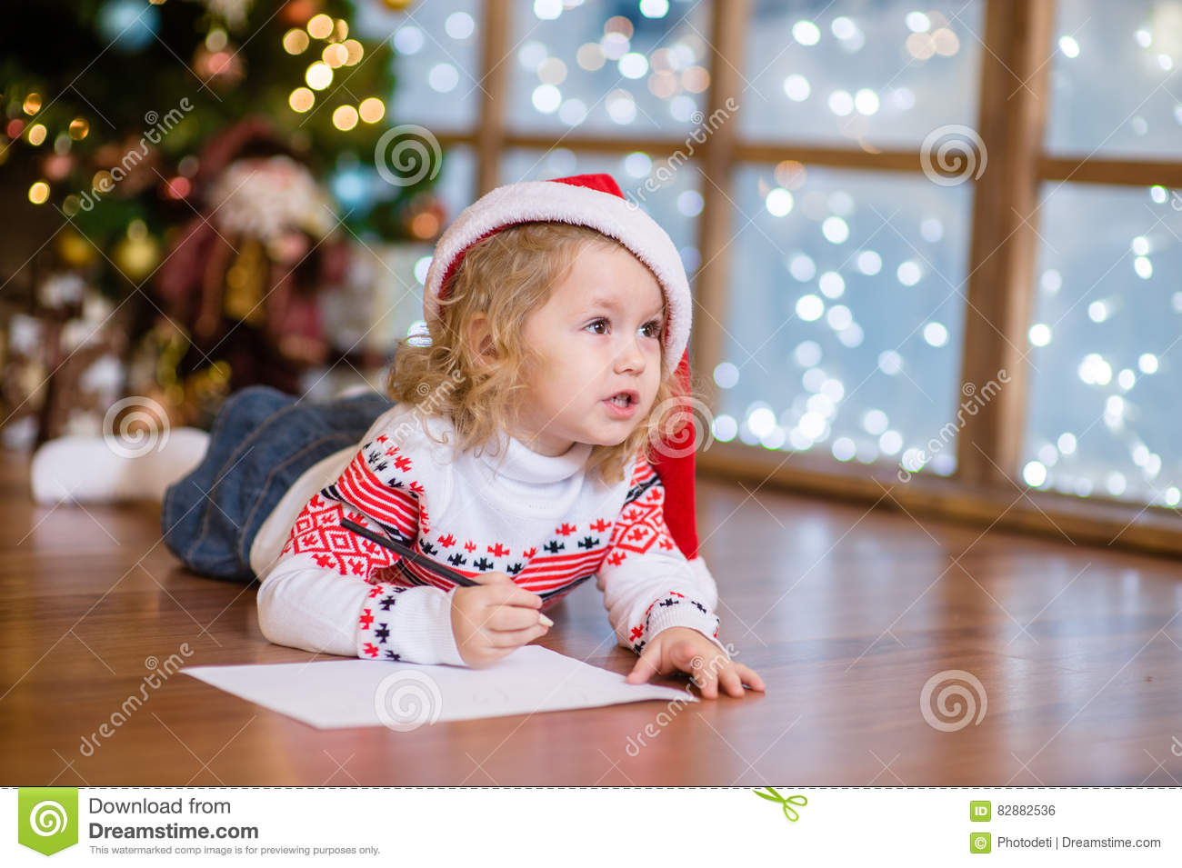 Christmas Child Writing Letter To Santa In Red Hat Stock